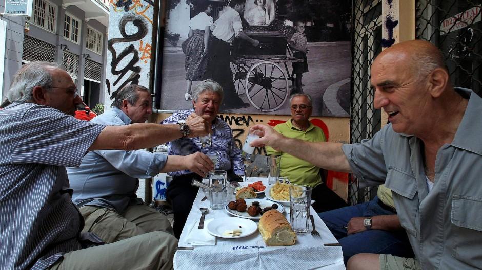 Eine Gruppe griechischer Männer trinkt Ouzo in einem Café in Athen.
