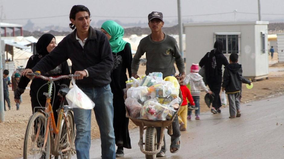 Syrische Flüchtlinge in Jordanien auf dem Weg zurück von der Nahrungsmittelausgabe der UN