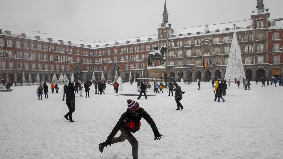 Winterlandschaft im Zentrum Madrids: Ein Mann wirft auf der zugeschneiten Plaza Mayor einen Schneeball.
