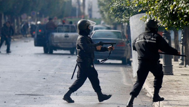 A police officer fires teargas to break up a protest during a demonstration in Tunis