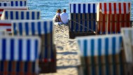 Urlauber sitzen am Strand in Rostock-Warnemünde