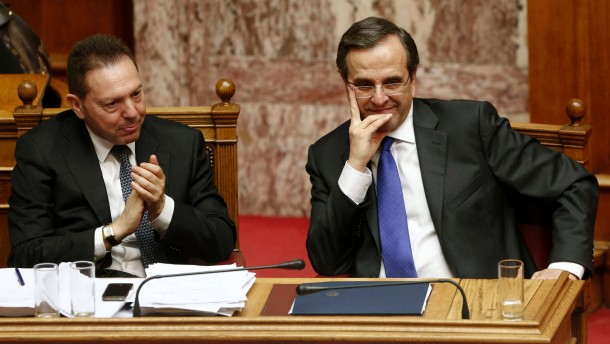 Finance minister Stournaras applauds as PM Samaras looks on during a parliament session in Athens