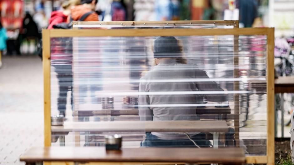 Gäste eines Hamburger Restaurants zwischen Plexiglas-Trennscheiben