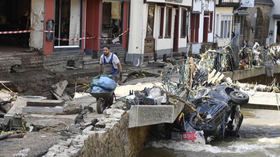 In Bad Münstereifel befördert ein Helfer Müll und Trümmer an der Erft entlang.