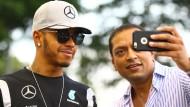 Noch ist er entspannt: Lewis Hamilton posiert in Singapur mit einem Fan