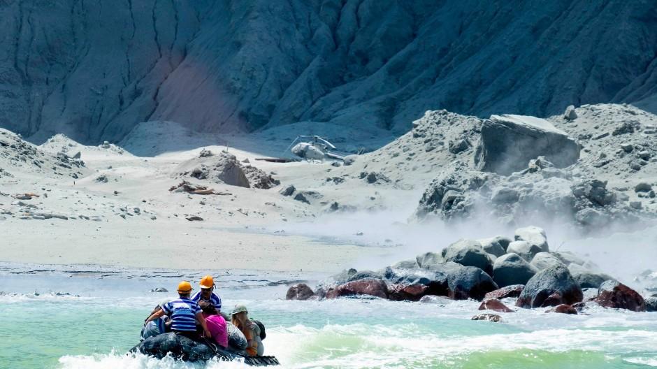 """Rettungskräfte verlassen in einem Boot """"White Islands"""". Laut der neuseeländischen Premierministerin Jacinda Ardern gibt es keine Hoffnung mehr, nach dem Vulkanausbruch Vermisste noch lebend zu finden."""