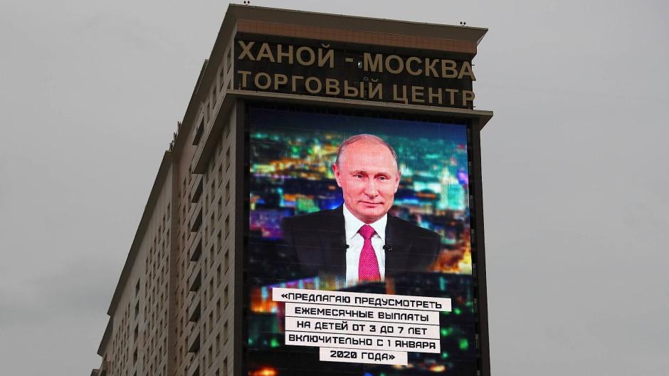 Über den Himmeln von Moskau: Die Jahresansprache von Wladimir Putin leuchtet von der Fassade eines Wohnhauses.