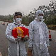 Ein Chinese kehrt aus einem Beerdigungsinstitut in Wuhan mit einer Urne zurück, die die Asche eines Angehörigen enthält.