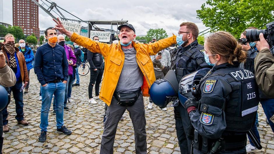Ein Demonstrant in Frankfurt weigert sich, eine Maske korrekt zu tragen und wird zur Identitätsfeststellung von der Polizei abgeführt.