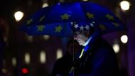 Es wird nass und dunkel über London: Ein Anti-Brexit-Demonstrant informiert sich über den Stand der Abstimmung im Parlament.