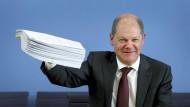 Ein dickes Hilfspaket: Bundesfinanzminister Olaf Scholz (SPD) hält während der Pressekonferenz zum Hilfspaket der Bundesregierung für Betroffene der Corona-Krise und einen Stapel Unterlagen in die Höhe.