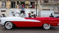 Unter der Flagge des großen Nachbarn: Kubaner fahren in einem amerikanischen Oldtimer durch Havanna.