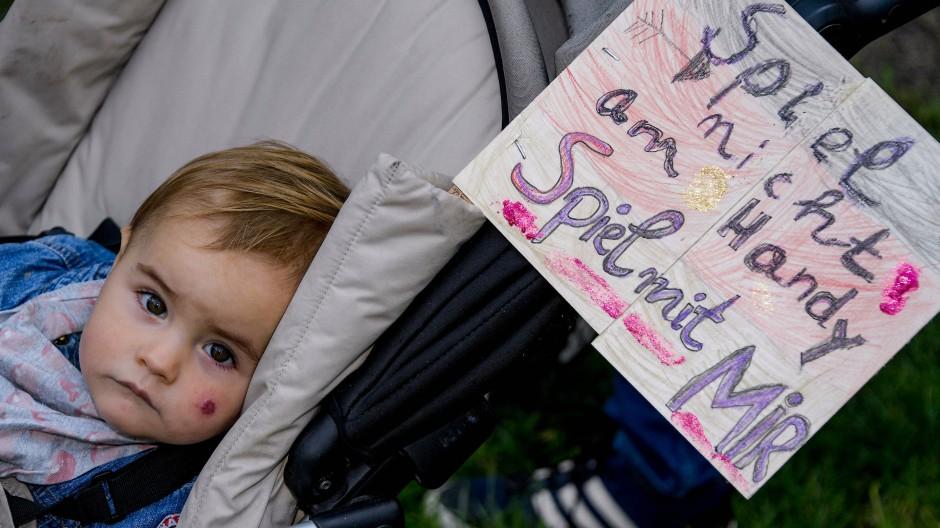 """Am Kinderwagen der ein Jahr alten Helen ist ein Schild mit der Aufschrift """"Spiel nicht am Handy - Spiel mit mir"""" befestigt."""