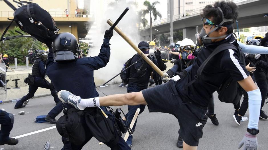 Ein Demonstrant tritt einen Polizisten während Auseinandersetzungen in den Rücken.
