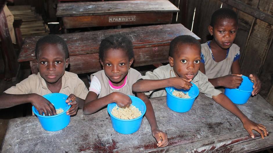 Kinder in Benin essen in einer Grundschule Reis.