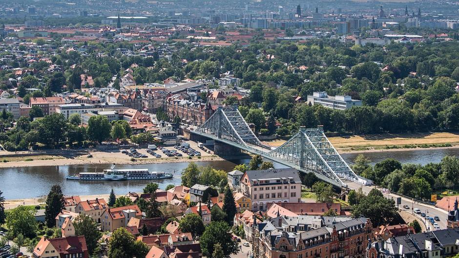 Der historische Schaufelraddampfer Leipzig der Sächsischen Dampfschiffahrt fährt auf der Elbe nahe der Brücke Blaues Wunder entlang.