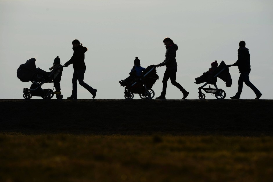 Drei Mütter schieben ihre Kinderwagen eine Landstraße entlang