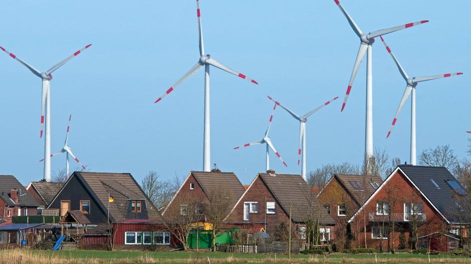 Windräder eines Windparks drehen sich dicht hinter einer Wohnsiedlung in Niedersachsen.