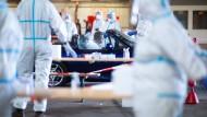 Mitarbeiter testen am Flughafen in Gütersloh in einem ehemaligen Hubschrauber-Hangar die Insassen eines Fahrzeuges auf Corona.