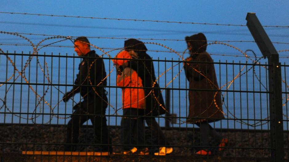 Ein französischer Polizist greift Flüchtlinge an den Schienen des Euro-Tunnels auf.