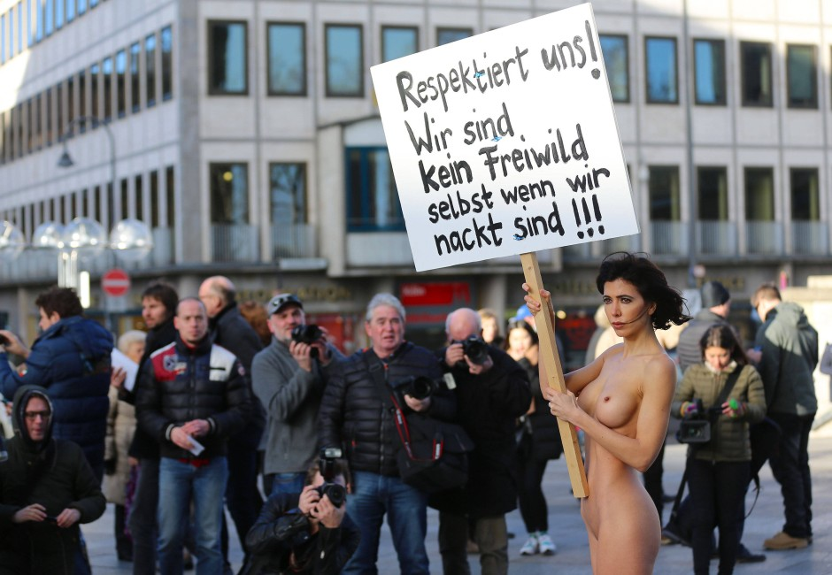 """Die Aktions-Künstlerin Milo Moire mit einem Plakat mit der Aufschrift """"Respektiert uns! Wir sind kein Freiwild selbst wenn wir nackt sind!!!"""""""