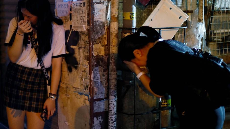 Zwei Frauen reiben sich in Hongkong die Augen, nachdem die Polizei Tränengas eingesetzt hatte.