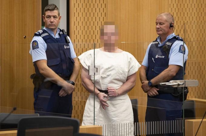 """Der Attentäter von Christchurch formt ein """"Okay""""-Zeichen mit seinen Fingern, als er dem Haftrichter vorgeführt wird."""