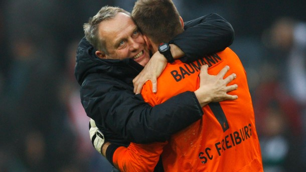 Freiburg's coach Streich hugs his goalkeeper Baumann after the German first division Bundesliga soccer match against Borussia Moenchengladbach in Moenchengladbach