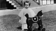 Der kleine japanische Thronfolger Akihito mit seinem Schaukelpferd im Garten des kaiserlichen Palasts in den Dreißiger Jahren. Akihito bestieg Anfang 1989 den japanischen Thron und wurde am 12.11.1990 offiziell zum 125. Kaiser von Japan ausgerufen. 1945 erlebte er als Elfjähriger die Kapitulation Japans. Seinem Vater wurde damals der göttliche Status aberkannt und die neue Verfassung verbot dem Kaiser jegliche Einmischung in die Politik.