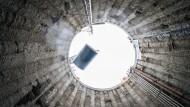 Abstieg: Am Kran schweben 45 Tonnen in den Schacht. Es ist das erste von vier Bohrerteilen.