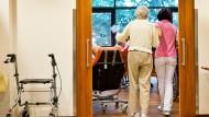 Eine auf Demenzkranke spezialisierte Pflegerin begleitet in Fürth eine ältere Frau (Archivbild)