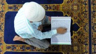 Junger Muslim bei der Koran-Lektüre