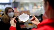 Ein Apotheker in Dortmund händigt eine FFP2-Maske aus.