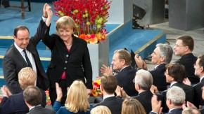 German Chancellor Merkel and French President Hollande hold up hands during the Nobel Peace Prize ceremony at the City Hall in Oslo