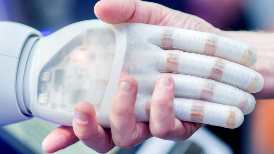 Ein Mann hält die Hand eines bionischen Roboters.
