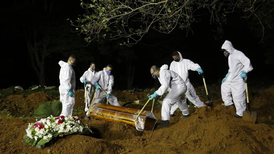 Friedhofsarbeiter senken den Sarg eines Covid-19-Opfers ins Grab auf einem Friedhof in São Paulo