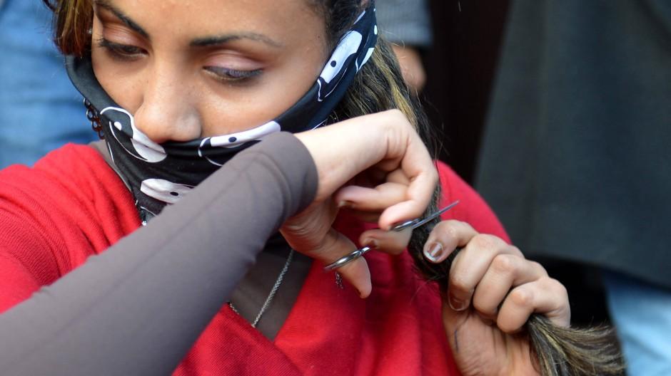 Aus Protest gegen die neue Verfassung schnitten sich einige Frauen am Dienstag auf dem Tahrir-Platz die Haare ab