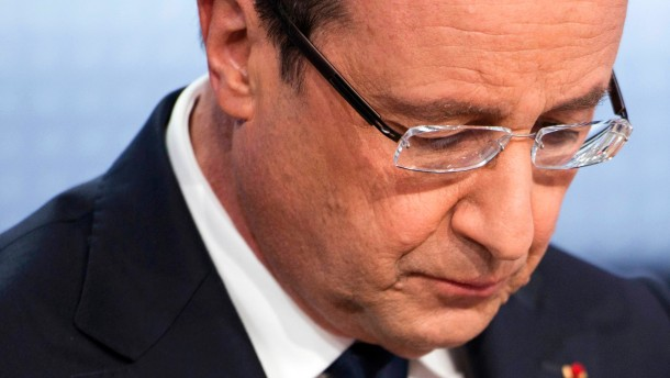 France's President Hollande reads his notes before appearing on France 2 television prime time news broadcast for an interview at their studios in Paris