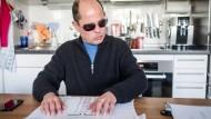 Gar nicht so einfach: Am Küchentisch liest Wolfgang Harders schon einmal die Schablone für die Wahl – mit den Fingern.