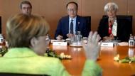 Bundeskanzlerin Angela Merkel sitzt WTO-Chef Roberto Azevêdo, Weltbank-Präsident Jim Yong Kim und IWF-Chefin Christine Lagarde gegenüber.