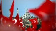 Menschen schwenken in Istanbul türkische Fahnen bei einer Gedenkveranstaltung zum zweiten Jahrestag des Putschversuchs.
