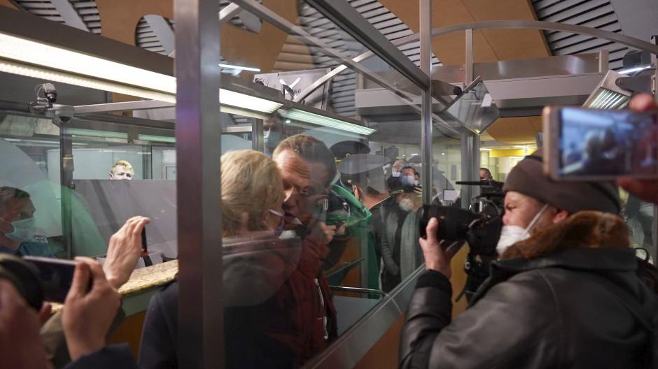 Alexej Nawalnyj (M) küsst seine Ehefrau Julia, während er von der Polizei bei der Passkontrolle nach der Ankunft am Flughafen Scheremetjewo festgehalten wird.