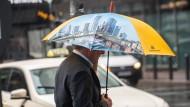 Ein Mann mit einem Werbeschirm der Commerzbank geht durch die regnerische Innenstadt von Frankfurt.