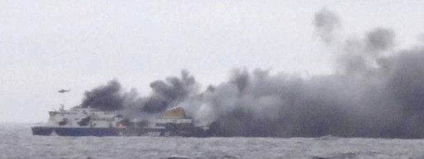 """Starker Rauch steigt von der nach wie vor brennenden Fähre """"Norman Atlantic"""" auf. Ein Helikopter bemüht sich um Hilfe aus der Luft."""