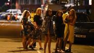 Polizisten kümmern sich nach dem Anschlag um eine Gruppe junger Frauen.