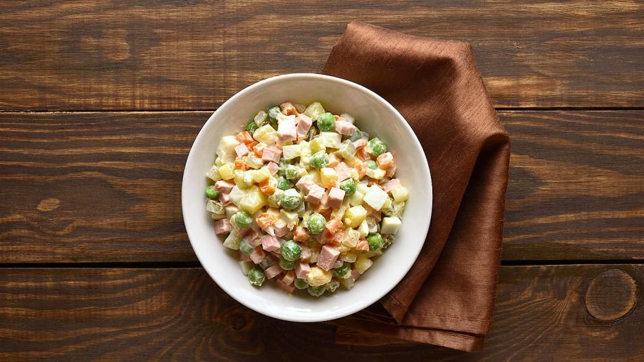 Es gibt zahllose Variationen: Aber in diesem Russischen Salat finden sich Erbsen, Karotten, Kartoffeln, Gewürzgurken, Kochschinken und natürlich Mayonnaise.