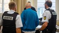 Der Angeklagte (Mitte) wird von Justizbeamten zu seinem Platz im Landgericht Ravensburg geführt.