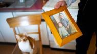 Der syrische Flüchtling Rafat Albuni steht in der Küche seiner Wohnung in Philippsthal und hält ein Bild seiner Brüder Zaid (rechts) und Taim in der Hand.