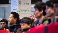 Demonstranten wenden sich im Flughafen München gegen eine geplante Sammelabschiebung nach Afghanistan.