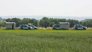 Polizeifahrzeuge stehen auf einem Feldwegen in Wiesbaden-Erbenheim, wo am Mittwoch die Leiche eines Mädchens gefunden wurde.